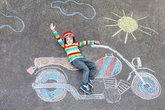 Pequeño niño en casco con la imagen de la motocicleta Foto de archivo