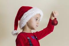 Pequeño niño en el casquillo de Papá Noel que mira el juguete de Navidad cerca del árbol de navidad Imágenes de archivo libres de regalías