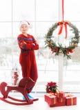 Pequeño niño en el interior blanco y rojo de la Navidad del día de fiesta Fotos de archivo