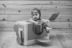 Pequeño niño en el piloto Costume Dreaming Of que pilota el avión foto de archivo