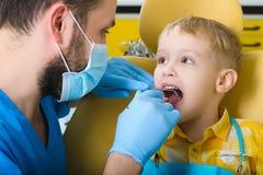 Pequeño niño, especialista que visita paciente en clínica dental Fotos de archivo libres de regalías