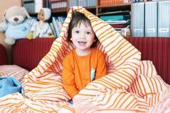 Pequeño niño feliz en cama en casa Imagen de archivo libre de regalías