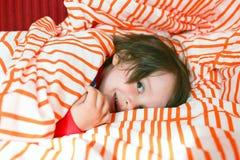 Pequeño niño feliz en cama en casa Fotos de archivo libres de regalías