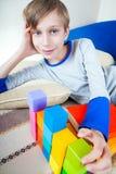Pequeño niño feliz lindo que miente en un sofá con los juguetes Foto de archivo