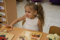 Pequeño niño feliz, niña pequeña rubia adorable, divirtiéndose que juega con los pedazos de junta del rompecabezas de sitt de la  Imagen de archivo