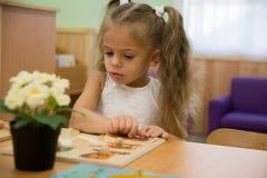 Pequeño niño feliz, niña pequeña rubia adorable, divirtiéndose que juega con los pedazos de junta del rompecabezas de sitt de la  Foto de archivo