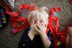 Pequeño niño feliz que celebra en un partido con confeti y la bola Fotos de archivo