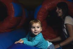 Pequeño niño feliz y muchacha adolescente que se divierten que juega en inflatabl Imágenes de archivo libres de regalías