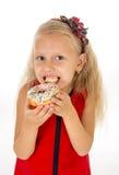 Pequeño niño femenino hermoso con el pelo rubio largo y el vestido rojo que come el buñuelo del azúcar con los desmoches encantad Imagenes de archivo