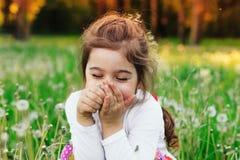Pequeño niño hermoso que sonríe con la flor del diente de león en su soleado fotos de archivo