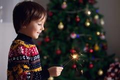 Pequeño niño hermoso que sostiene la bengala ardiente en nuevo Year& x27; s Ev Fotografía de archivo libre de regalías