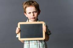 Pequeño niño infeliz que muestra la pizarra vacía de la escritura a la reflexión expresa Foto de archivo
