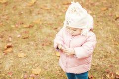 Pequeño niño lindo de la muchacha que se divierte en parque en ropa caliente del otoño y x28; imagen de archivo