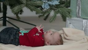 Pequeño niño lindo debajo del árbol de navidad feliz metrajes