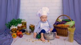 Pequeño niño lindo del bebé en la cocina que cocina en cacerola