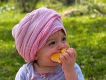 Pequeño niño lindo del bebé que come la fruta anaranjada Fotografía de archivo libre de regalías