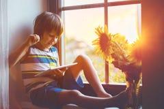 Pequeño niño lindo del niño, jugando en la tableta en una ventana Imagen de archivo