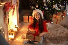 Pequeño niño lindo en el sombrero de Papá Noel con el regalo de la Navidad que se sienta delante de la chimenea cerca de árbol de fotos de archivo