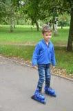 Pequeño niño lindo, muchacho, patinando en el parque, primavera imagenes de archivo