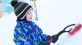 Pequeño niño lindo que ayuda a cepillar una nieve de un coche Niño pequeño que usa la herramienta para limpiar el coche de los pa imagen de archivo libre de regalías