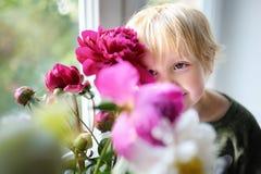 Pequeño niño lindo y ramo asombroso de peonías blancas y púrpuras foto de archivo libre de regalías