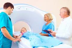 Pequeño niño paciente entre el personal médico listo para la exploración del ct imagen de archivo