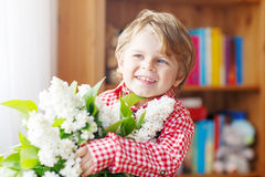 Pequeño niño pequeño adorable con la flor blanca floreciente de la lila Imagen de archivo libre de regalías