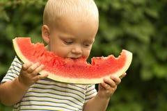 Pequeño niño pequeño divertido con los pelos rubios que come la sandía en jardín del verano Niño que prueba el bocado sano Comida imágenes de archivo libres de regalías
