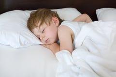 Pequeño niño pequeño dulce que duerme en su cama Imagenes de archivo
