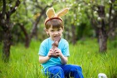 Pequeño niño pequeño feliz que come el chocolate y que lleva el bollo de Pascua Foto de archivo