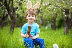 Pequeño niño pequeño feliz que come el chocolate y que lleva los oídos del conejito de pascua, sentándose en jardín floreciente e Foto de archivo
