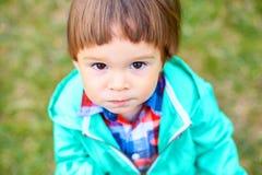 Pequeño niño pequeño lindo en un parque que mira la cámara Imagen de archivo