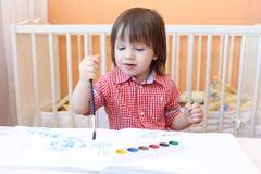 Pequeño niño precioso con las pinturas del color de agua Imagen de archivo libre de regalías