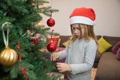 Pequeño niño que adorna el árbol de navidad Foto de archivo libre de regalías
