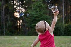 Pequeño niño que alcanza arriba para la burbuja de jabón Imágenes de archivo libres de regalías