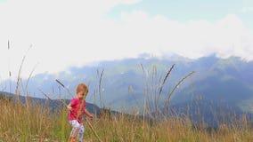 Pequeño niño que camina a través de la hierba alta en las montañas en un día de verano caliente HD lleno 1920x1080 almacen de video
