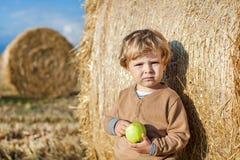 Pequeño niño que come la manzana con una bala de heno grande en campo Imagen de archivo libre de regalías