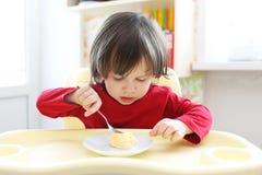 Pequeño niño que come los huevos revueltos Nutrición sana Imágenes de archivo libres de regalías