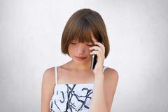 Pequeño niño que comunica sobre el teléfono elegante con sus padres mientras que mira abajo Muchacha bonita con el pelo corto y f Fotos de archivo