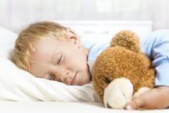 Pequeño niño que duerme en cama Imágenes de archivo libres de regalías