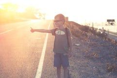 Pequeño niño que hace autostop Fotos de archivo libres de regalías