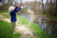 Pequeño niño que juega afuera por el río, arena que lanza en el agua foto de archivo