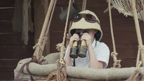 Pequeño niño que juega al explorador, mirando con la situación binocular en balón de aire almacen de metraje de vídeo