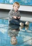Pequeño niño que juega con el teléfono móvil y su reflexión en el piso Imagen de archivo
