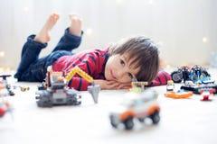 Pequeño niño que juega con las porciones de juguetes plásticos coloridos interiores Foto de archivo libre de regalías