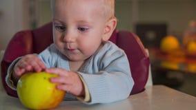 Pequeño niño que juega con una manzana almacen de video