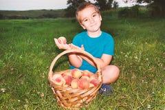 Pequeño niño que muestra y que sostiene en su mano un melocotón imagen de archivo libre de regalías