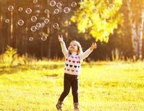 Pequeño niño que se divierte con el jabón de las burbujas en día soleado del otoño Fotos de archivo