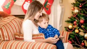 Pequeño niño pequeño que se sienta con la madre al lado del árbol de navidad y de historietas de observación en el teléfono móvil foto de archivo libre de regalías