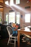 Pequeño niño que se sienta en la mesa de desayuno que bebe la taza de Sippy en Sunny Morning fotos de archivo libres de regalías